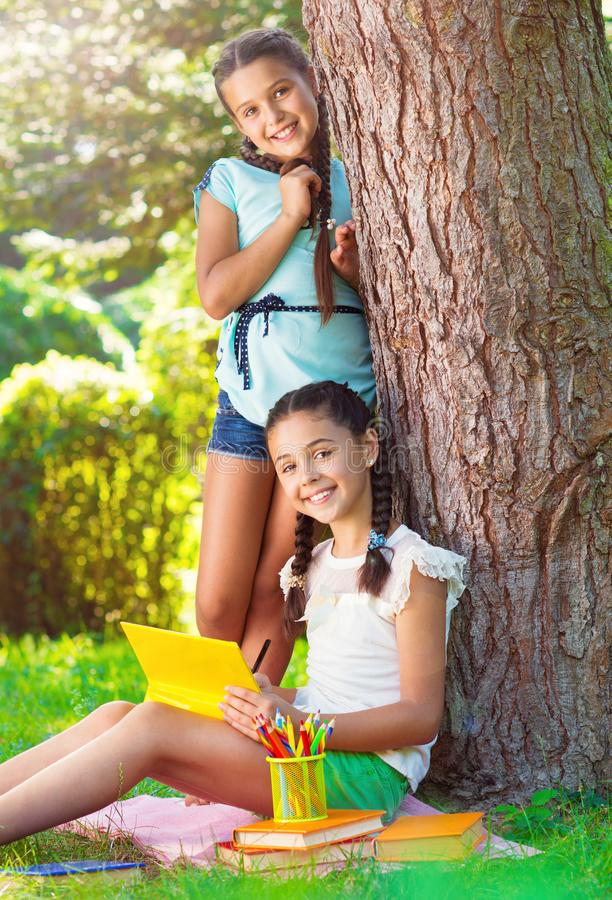 Two pretty little girls reading in park stock photography