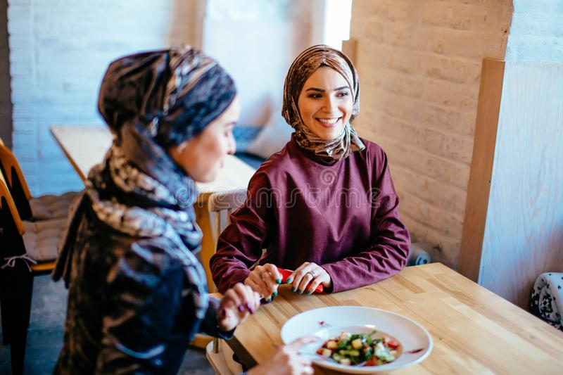 Two Muslim women in cafe, friends meeting. Two pretty Muslim women in cafe, friends meeting royalty free stock image