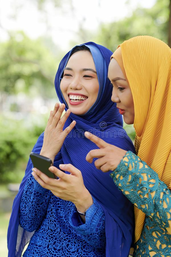 Laughing muslim women with smartphone stock images