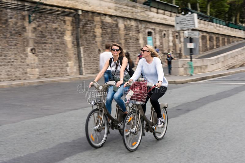 Two pretty Parisian girls who ride a velib. Two Parisian bicycle ride on the docks without cars of the Seine in Paris