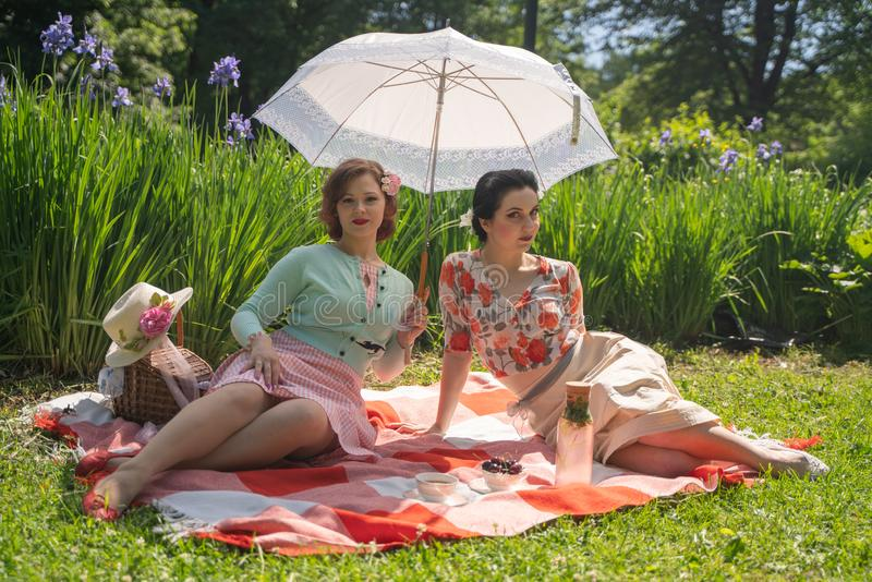 Two pretty pin up ladies having nice picnic in the city park in a sunny day together. girls friends enjoy hot summer weather. beau royalty free stock photography