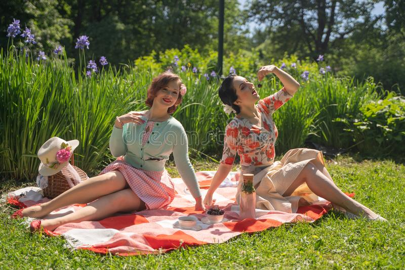 Two pretty pin up ladies having nice picnic in the city park in a sunny day together. girls friends enjoy hot summer weather. beau stock images