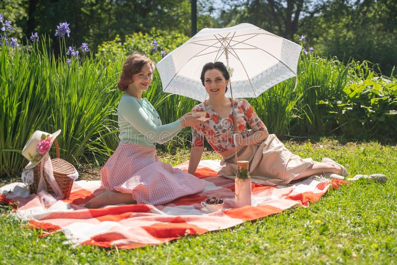 Two pretty pin up ladies having nice picnic in the city park in a sunny day together. girls friends enjoy hot summer weather. beau royalty free stock photos