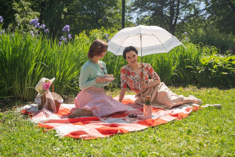 Two pretty pin up ladies having nice picnic in the city park in a sunny day together. girls friends enjoy hot summer weather. beau stock photos