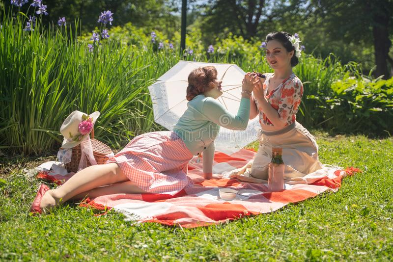Two pretty pin up ladies having nice picnic in the city park in a sunny day together. girls friends enjoy hot summer weather. beau stock photography