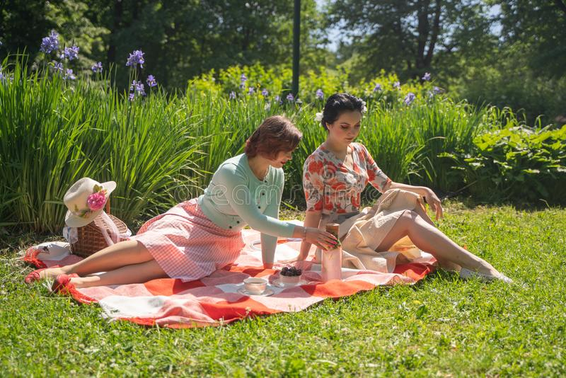 Two pretty pin up ladies having nice picnic in the city park in a sunny day together. girls friends enjoy hot summer weather. beau stock photo