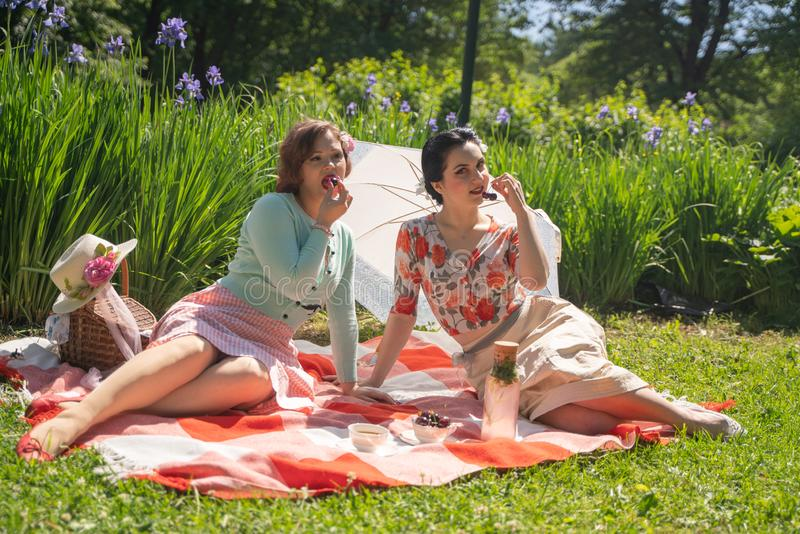 Two pretty pin up ladies having nice picnic in the city park in a sunny day together. girls friends enjoy hot summer weather. beau royalty free stock photo