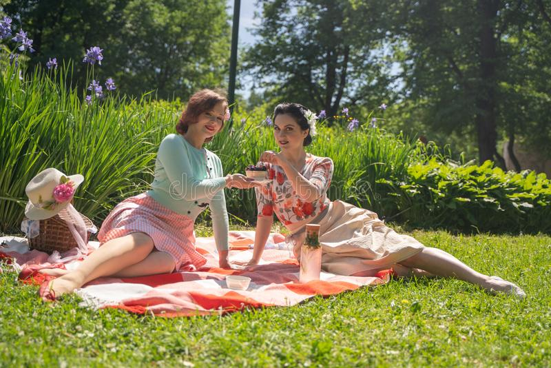 Two pretty pin up ladies having nice picnic in the city park in a sunny day together. girls friends enjoy hot summer weather. beau royalty free stock images