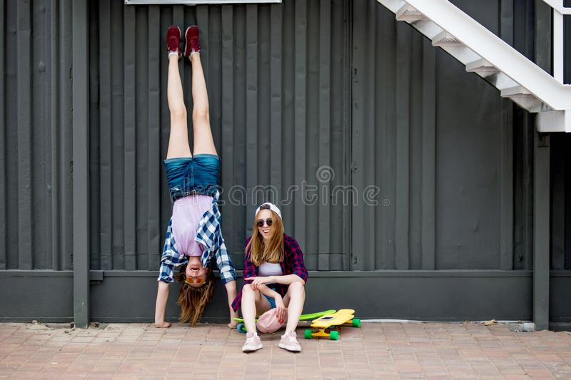 Two pretty smiling blond girls wearing checkered shirts, caps and denim shorts are balancing in front of the black wall royalty free stock photos