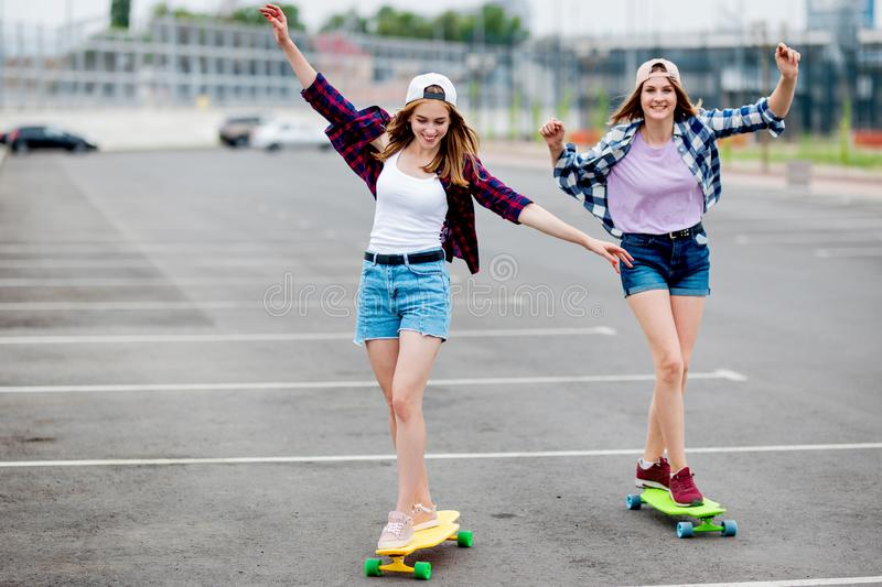 Two pretty smiling blond girls wearing checkered shirts, caps and denim shorts are longboarding on the empty car park stock image