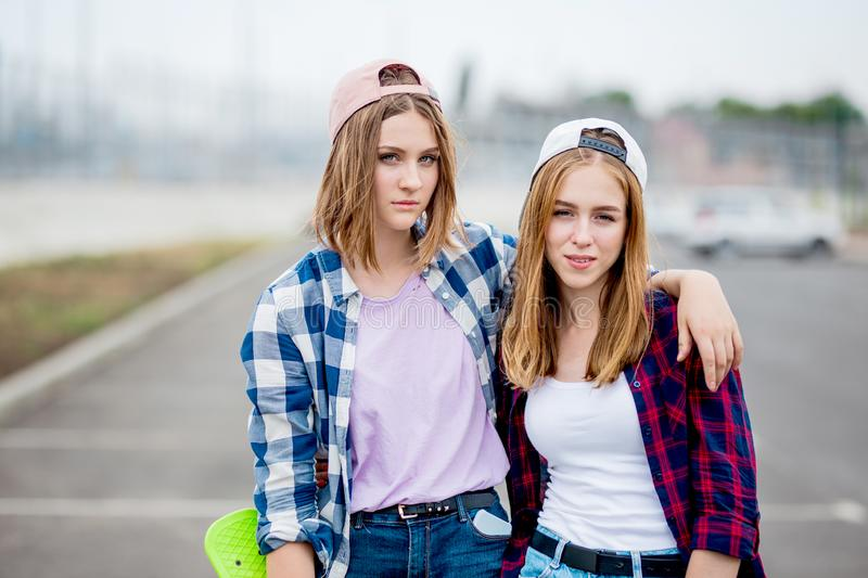 Two pretty smiling blond girls wearing checkered shirts, caps and denim shorts are standing on the empty car park with stock photography