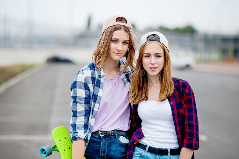 Two pretty smiling blond girls wearing checkered shirts, caps and denim shorts are standing on the empty car park with stock photos