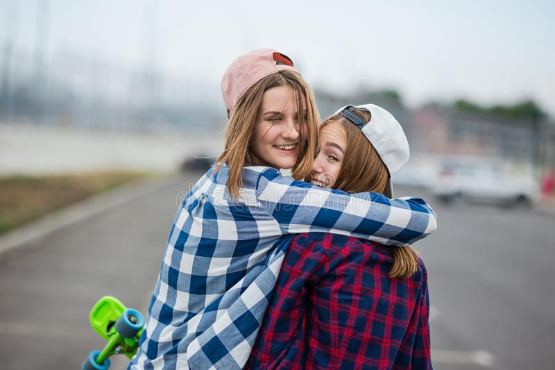 Two pretty smiling blond girls wearing checkered shirts, caps and denim shorts are standing and hugging on the empty car royalty free stock images