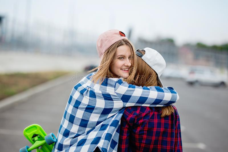 Two pretty smiling blond girls wearing checkered shirts, caps and denim shorts are standing and hugging on the empty car stock image