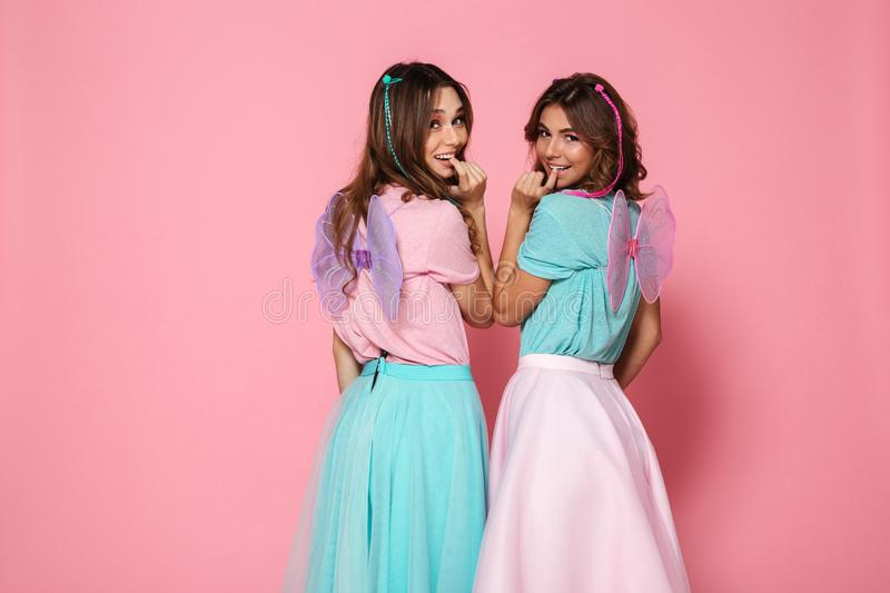 Two pretty smiling girls dressed like fairies with wings royalty free stock photos