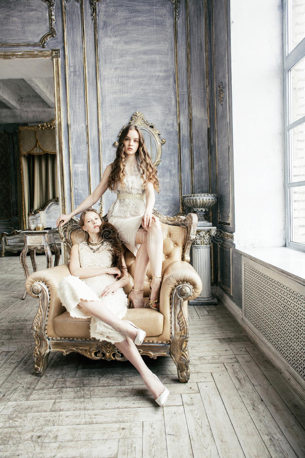 Two pretty twin sister blond curly hairstyle girl in luxury house interior together, rich young people concept stock photos