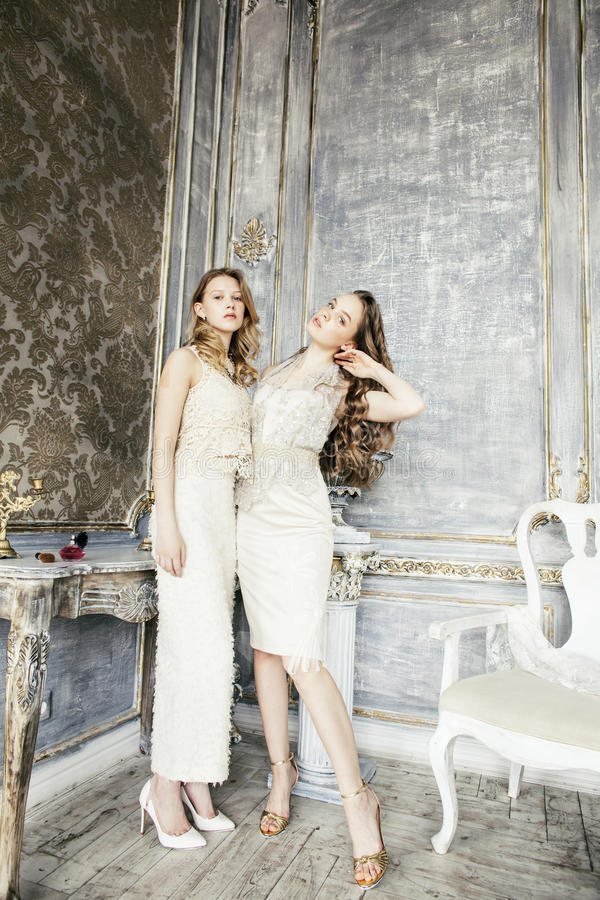 Two pretty twin sister blond curly hairstyle girl in luxury house interior together, rich young people concept royalty free stock photography