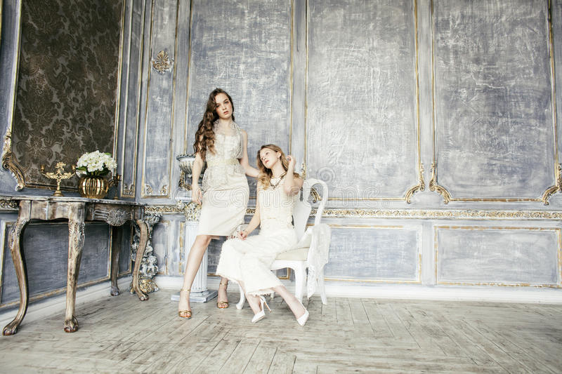 Two pretty twin sister blond curly hairstyle girl in luxury house interior together, rich young people concept stock photography