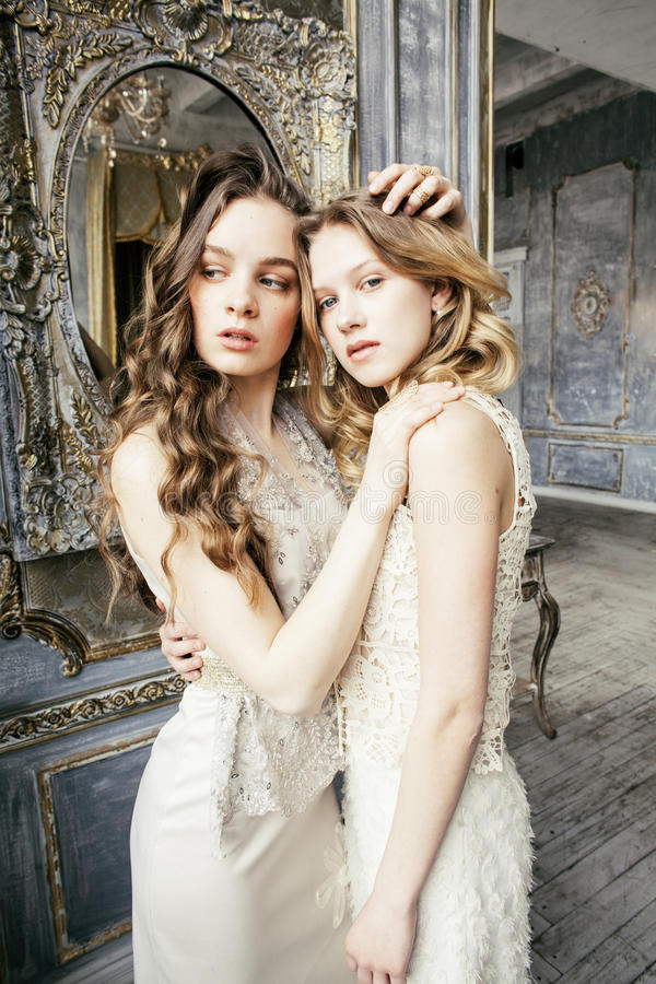 Two pretty twin sister blond curly hairstyle girl in luxury house interior together, rich young people concept stock photo