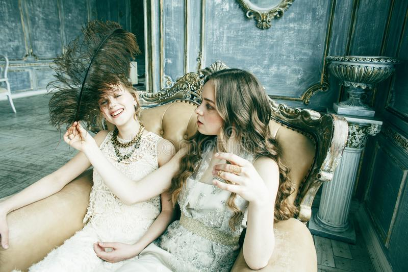 Two pretty twin sister blond curly hairstyle girl in luxury house interior together, rich young people concept royalty free stock image