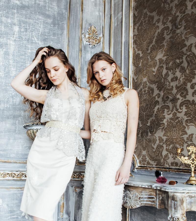 Two pretty twin sisters blond curly hairstyles in luxury house interior together, rich young people concept royalty free stock photos