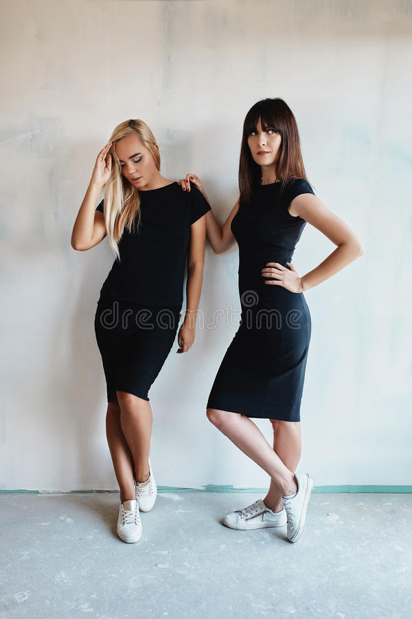 Two pretty woman in a black dress indoor stock image