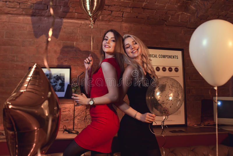 Two pretty women in cocktail dresses posing with balloons at birthday party in stylish cafe royalty free stock photo