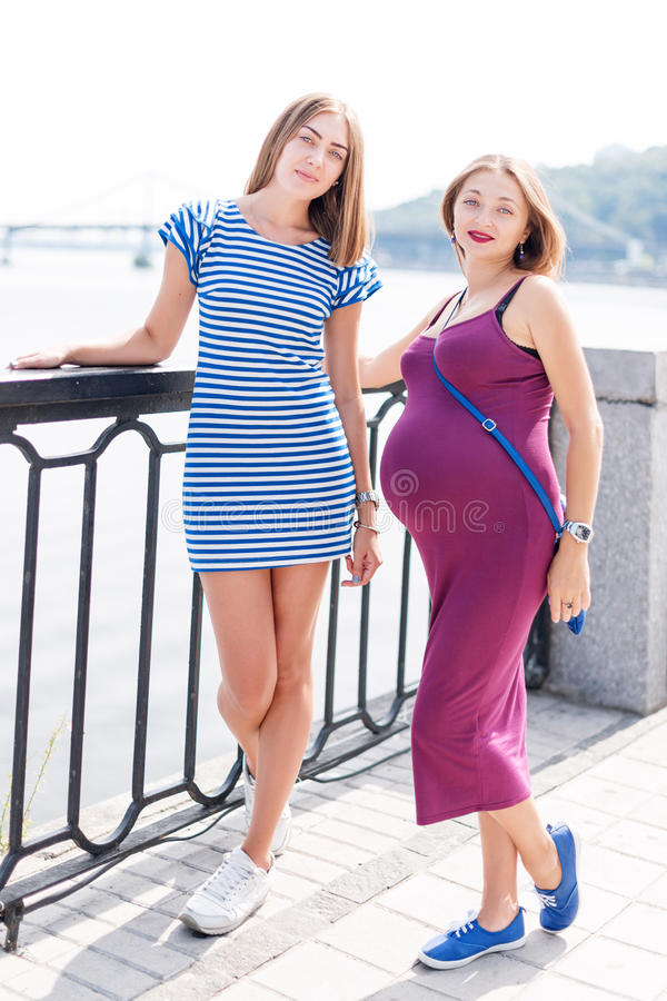 Two pretty women walking on city embankment, happy family. Samesex lesbian family, pregnant couple. Two pretty women walking on city embankment, happy family royalty free stock image