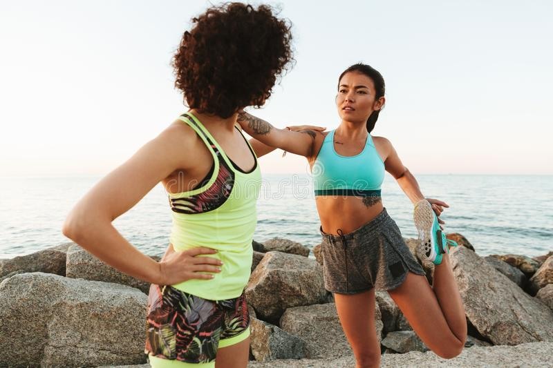 Two pretty young fitness women warming up outdoors stock images
