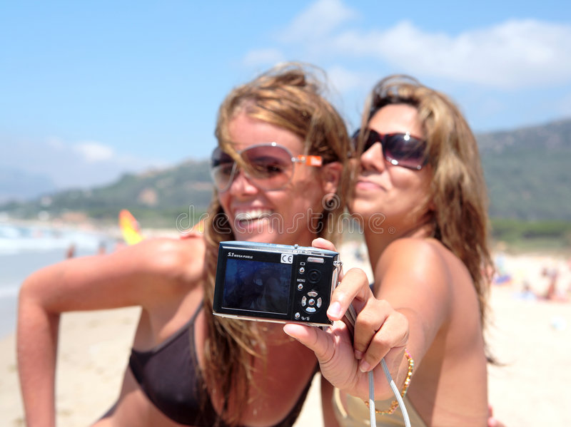 Two pretty young girlfriends taking a photo of themselves with c stock photography