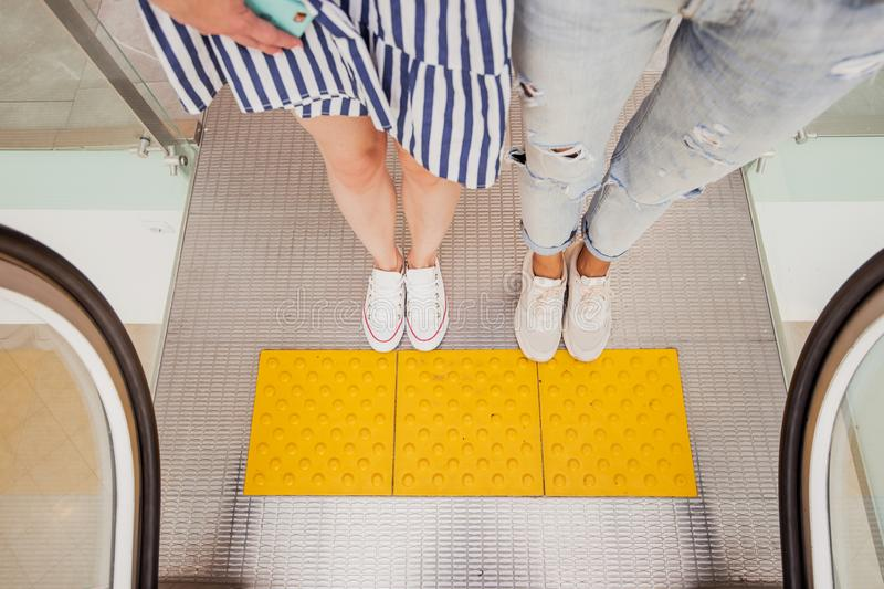 Two pretty young slim girls with dark hair,wearing casual style,stand at the escalator next to each other in a modern. Mall stock photo