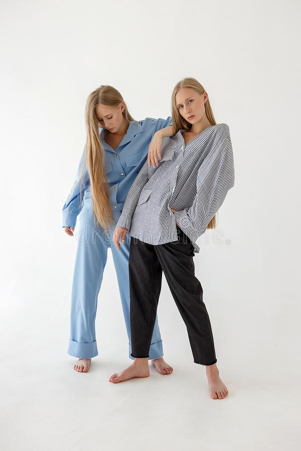 Two pretty young twin sisters with long blond hair posing on white background in oversize clothes. Fashion photoshoot royalty free stock photo