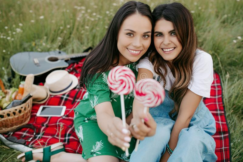 Two pretty young women with beatiful smile sitting down on the picnic blanket with candies. stock photography