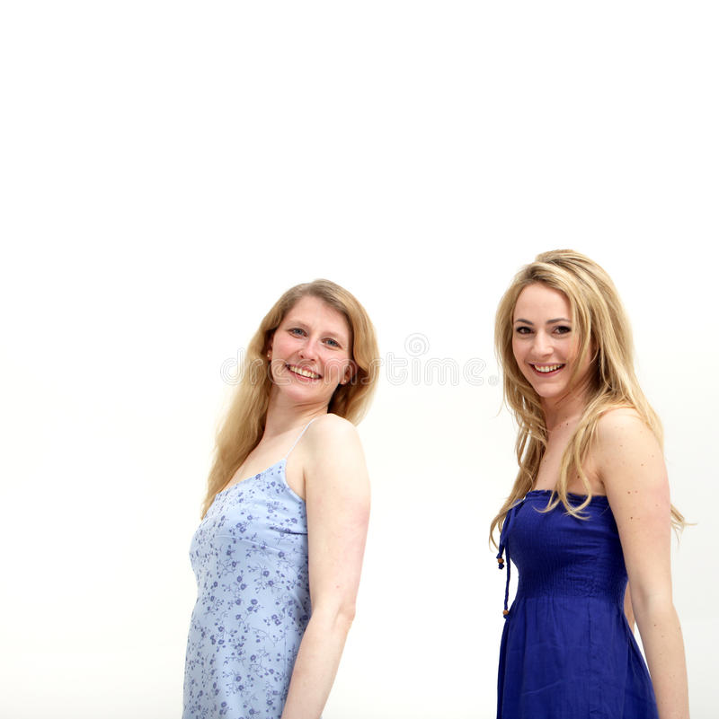 Two Pretty young women smiling at the camera. While standing against a white background royalty free stock image