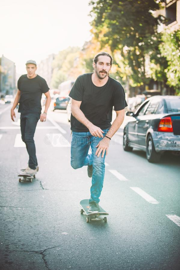 Two pro skateboard rider ride skate through cars on street. Two pro skateboard rider ride skate in front of the car on the city road street through traffic jam royalty free stock photos