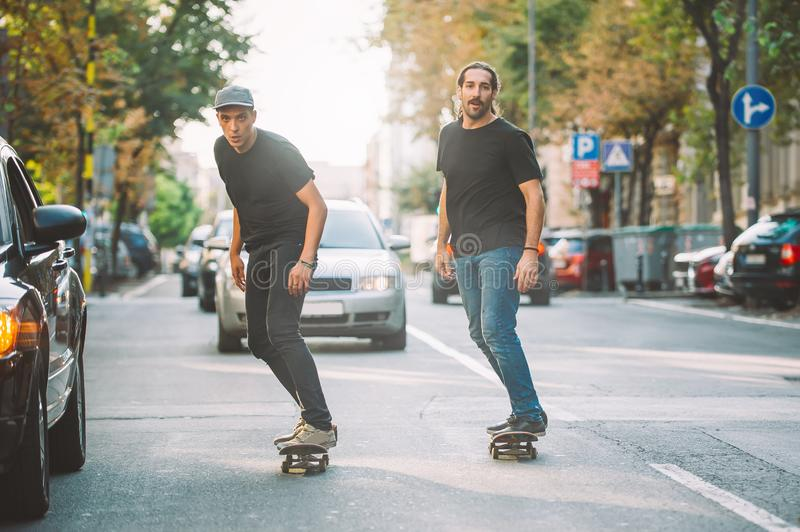 Two pro skateboard rider ride skate through cars on street. Two pro skateboard rider ride skate in front of the car on the city road street through traffic jam stock images