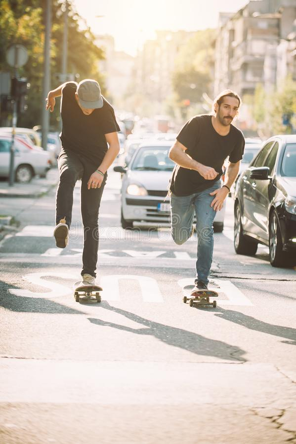 Two pro skateboard rider ride skate through cars on street. Two pro skateboard rider ride skate in front of the car on the city road street through traffic jam royalty free stock photography