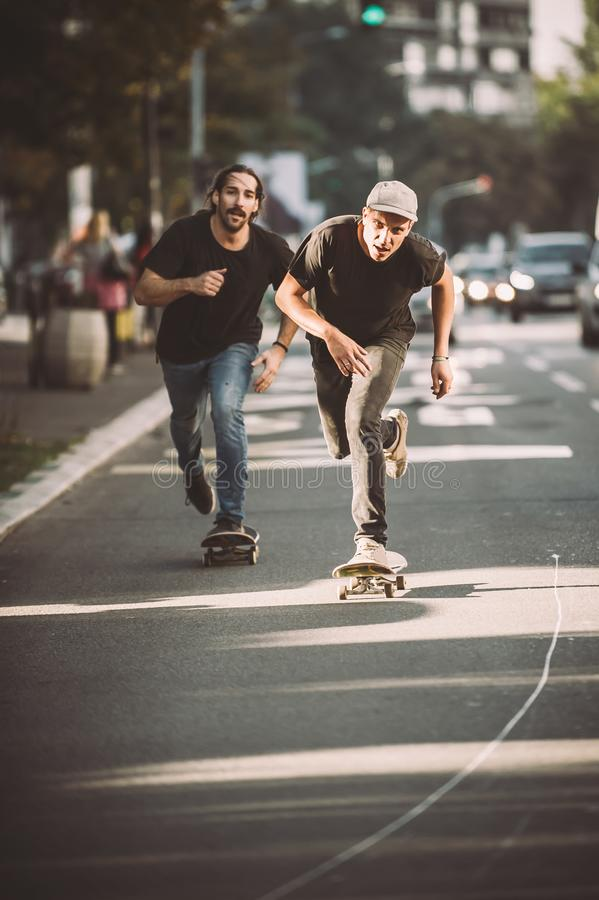 Two pro skateboard rider ride skate through cars on street. Two pro skateboard rider ride skate in front of the car on the city road street through traffic jam stock photo