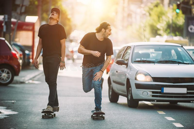 Two pro skateboard rider ride skate through cars on street. Two pro skateboard rider ride skate in front of the car on the city road street through traffic jam royalty free stock photo
