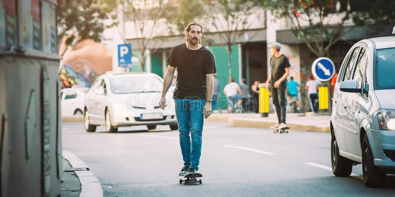 Two pro skateboard rider ride skate through cars on street. Two pro skateboard rider ride skate in front of the car on the city road street through traffic jam royalty free stock images