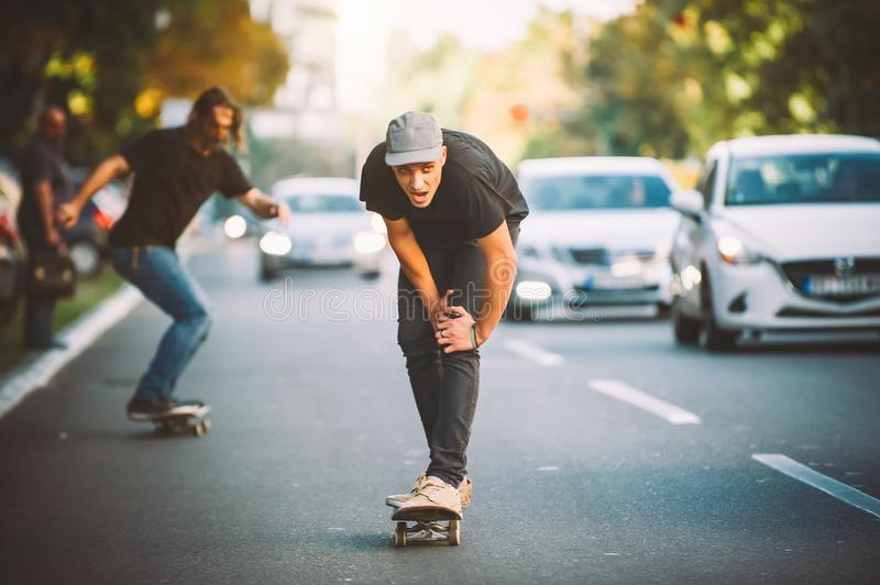 Two pro skateboard rider ride skate through cars on street. Two pro skateboard rider ride skate in front of the car on the city road street through traffic jam royalty free stock image