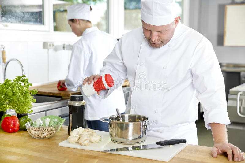 Two professional chefs preparing food in large kitchen. Professional chef add salt in food at a industrial kitchen in hotel or restaurant. Assistant or chef royalty free stock photography