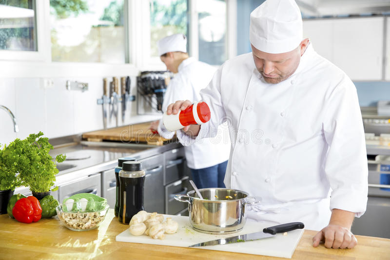 Two professional chefs preparing food in large kitchen. Professional chef add salt in food at a industrial kitchen in hotel or restaurant. Assistant or chef stock images