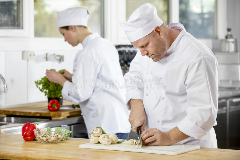 Two professional chefs preparing vegetables in large kitchen. Professional chef chops up mushrooms and makes food in industrial kitchen stock photo