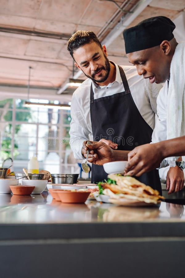 Chefs cooking new food dish in kitchen. Two professional chefs working in restaurant kitchen. Chefs cooking new food dish at commercial kitchen stock images