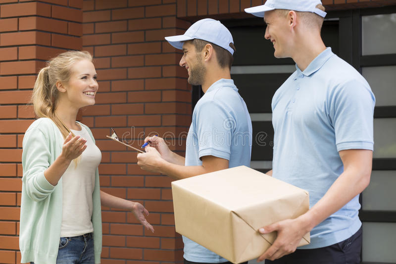 Two professional couriers delivering a package stock images