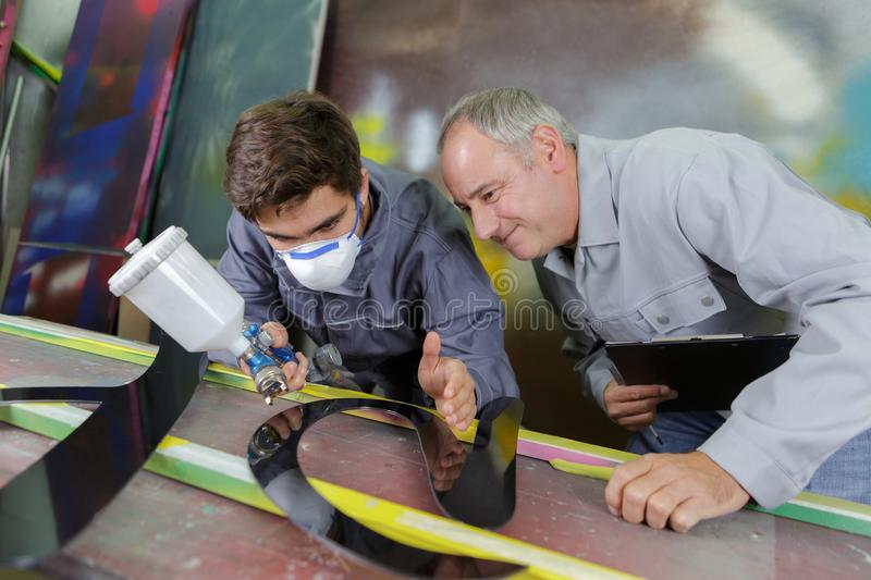 Two professional factory painters workers painting metal royalty free stock images