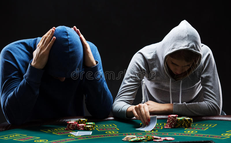 Two professional poker players sitting at a table. Two professional poker players sitting at a poker table on black background trying to hide his expressions stock image