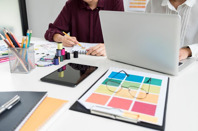Two professional stylish fashion designer working as fashion designers measure as sketches in workshop of new collection in royalty free stock photos