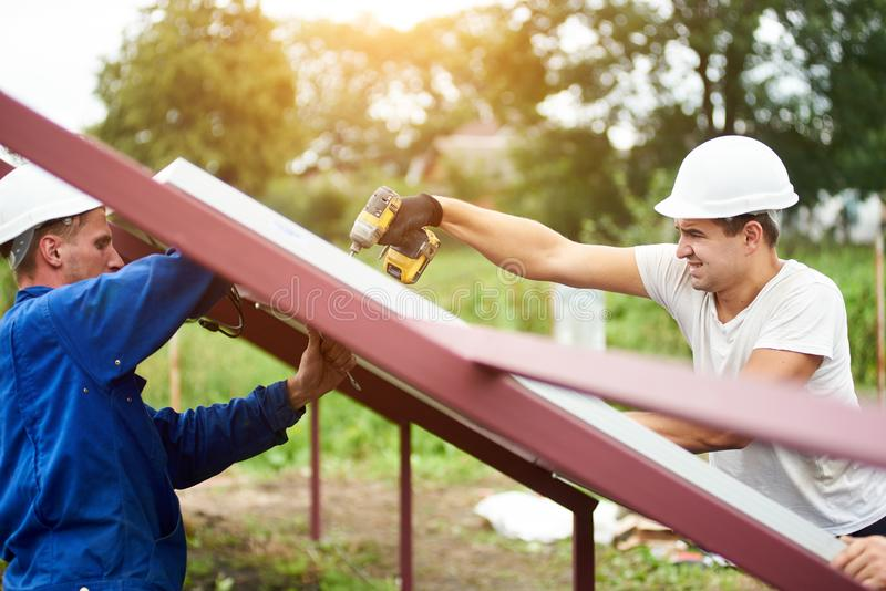 Installation of stand-alone exterior photo voltaic panels system. Renewable green energy generation. Two professional technicians connecting solar photo voltaic stock images